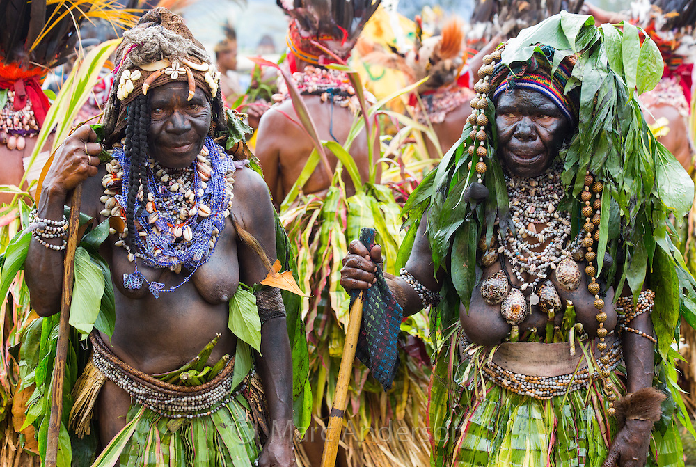 Old women with their faces painted black and wearing traditional dresses of beads and leaves at the Goroka show in Papua New Guinea.