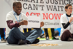 "11 December 2019, Madrid, Spain: ACT Alliance, Lutheran World Federation and World Council of Churches participants at COP25 illustrate the lack of balance in finance of the global climate response, where most ofthe finance is put into mitigation, some into adaptation, but very little into loss and damage, even though 'that's where the people are'. 'What do we want? Climate justice. When do we want it? Now!"" they chanted."