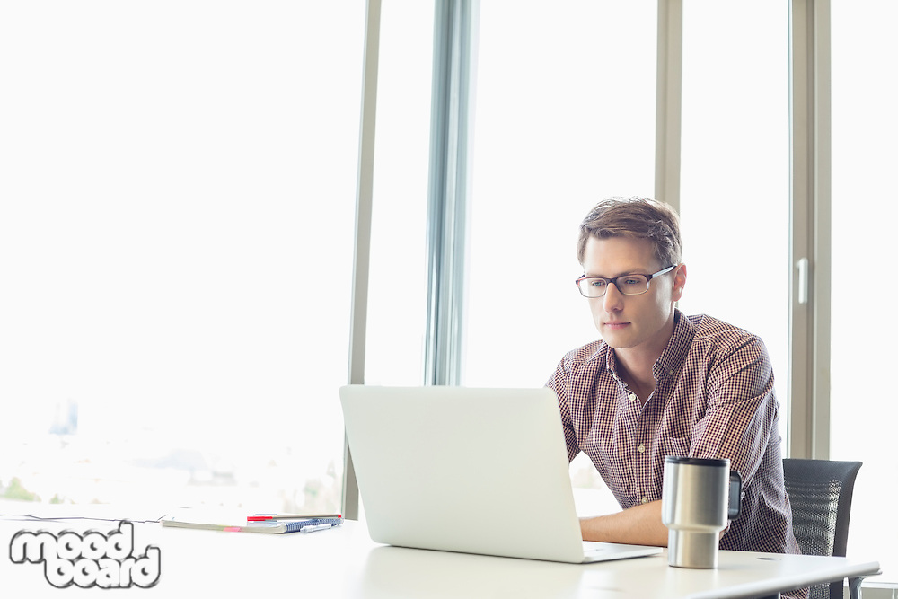 Mid-adult businessman using laptop at desk in creative office