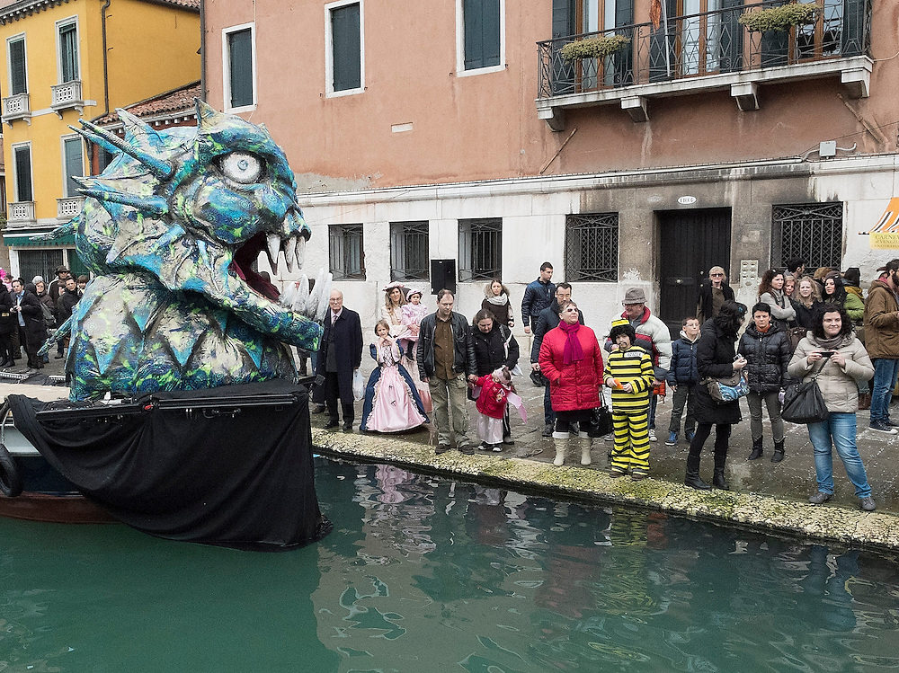 VENICE, ITALY - FEBRUARY 16:  Tourists stands on the bank of Canaregio Canal for the passage of the traditional regatta which officially opens the Venice Carnival  on February 16, 2014 in Venice, Italy. The 2014 Carnival of Venice will run from February 15 to March 4 and includes a program of gala dinners, parades, dances, masked balls and music events.  (Photo by Marco Secchi/Getty Images)