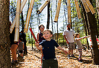 Young meistro John Lyman plays a tune in the Music Area of Prescott Farm's Natural Playscape during their grand opening on Saturday morning.  (Karen Bobotas/for the Laconia Daily Sun)