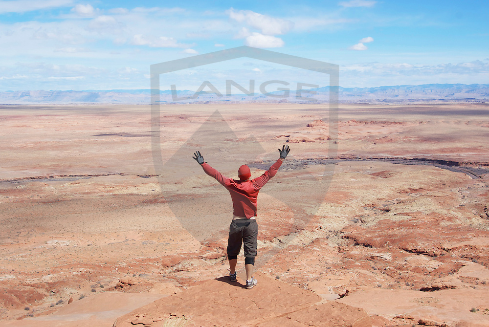 man with red shirt and arms raised into the air above the san rafael desert sandstone landscape, southeastern utah, usa