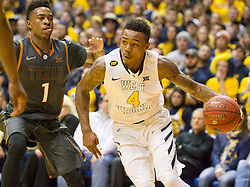 West Virginia Mountaineers guard Daxter Miles Jr. (4) drives past Texas Longhorns guard Isaiah Taylor (1) during the second half at the WVU Coliseum.