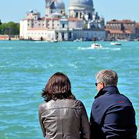 Middle-aged Couple Viewing Santa Maria della Salute in Venice, Italy<br /> Other than ferries and gondolas, Venice is a pedestrian-only city so you will walk all day trying to explore its countless historic, beautiful sites.  Periodically, when your legs begin to hurt, you just need to take a break like this couple sitting along a major promenade called Riva degli Schiavoni with a wonderful view of Santa Maria della Salute.