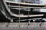 People ride bicycles on a bridge with spans and ramps of an expressway overpass behind. Nihonbashi, Tokyo, Japan. Thursday September 15th 2011