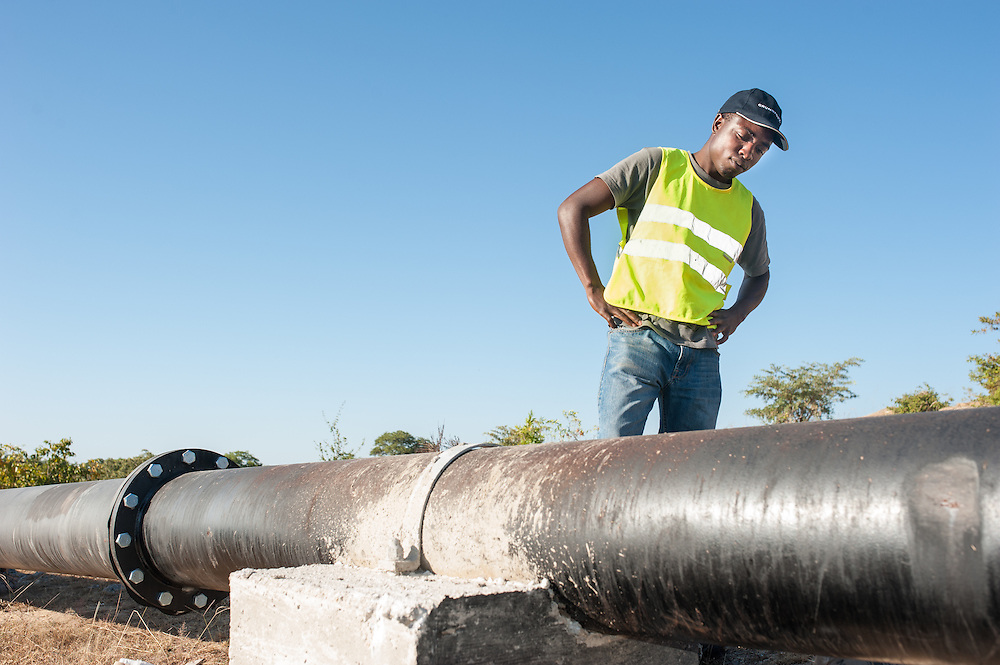 CAPTION: Farai, who serves as Site Supervisor at the Bindagombe Irrigation Scheme, inspects pipe work leading from the newly-built reservoir to the village below. LOCATION: Mawoneke Village, Chivi District, Masvingo Province, Zimbabwe. INDIVIDUAL(S) PHOTOGRAPHED: Farai Mwaisowa.