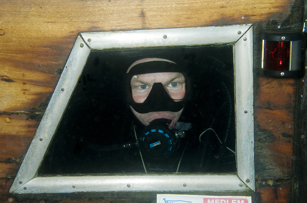 Diver inside the wreck of a sunken boat. Location : Stavanger, Norway