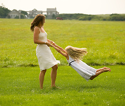 Mother twirling her daughter on a lawn in East Hampton, NY