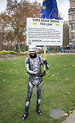 © Licensed to London News Pictures. 26/11/2018. London, UK. A campaigner dressed as film character 'Robocop'  holds a placard alleging that the Vote Leave campaign broke the law - outside Parliament. Prime Minister Theresa May will update the House of Commons later on the EU withdrawal deal agreed by the 27 member states at the weekend. Photo credit: Peter Macdiarmid/LNP