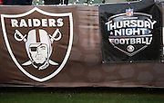 Signs on the front row include a team logo and a banner for NFL Network Thursday Night Football on CBS before the Oakland Raiders NFL week 12 regular season football game against the Kansas City Chiefs on Thursday, Nov. 20, 2014 in Oakland, Calif. The Raiders won their first game of the season 24-20. ©Paul Anthony Spinelli