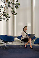 Business woman using laptop in office lobby