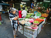 04 JANUARY 2016 - BANGKOK, THAILAND:         A woman shops for produce at a vegetable stand in Bang Chak Market on the last day it was open. The market closed January 4, 2016. The Bang Chak Market serves the community around Sois 91-97 on Sukhumvit Road in the Bangkok suburbs. About half of the market has been torn down. Bangkok city authorities put up notices in late November that the market would be closed by January 1, 2016 and redevelopment would start shortly after that. Market vendors said condominiums are being built on the land.     PHOTO BY JACK KURTZ