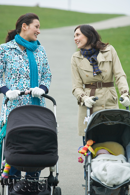 Two mothers with strollers in park having chat