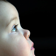 A ten month old baby girl peering out of the window while playing with her toys. Photo Tim Clayton