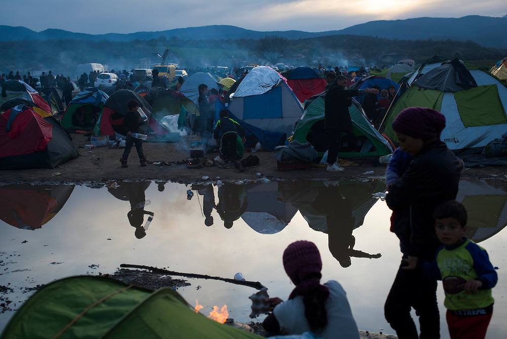 Refugees are reflected in a puddle at a camp on the Macedonian (FYROM) border on March 8, 2016 in Idomeni, Greece.