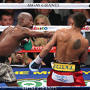 LAS VEGAS, NV - SEPTEMBER 13: Floyd Mayweather Jr. (L) throws a right cross at Marcos Maidana during their WBC/WBA welterweight title fight at the MGM Grand Garden Arena on September 13, 2014 in Las Vegas, Nevada. (Photo by Alex Menendez/Getty Images) *** Local Caption *** Floyd Mayweather Jr; Marcos Maidana