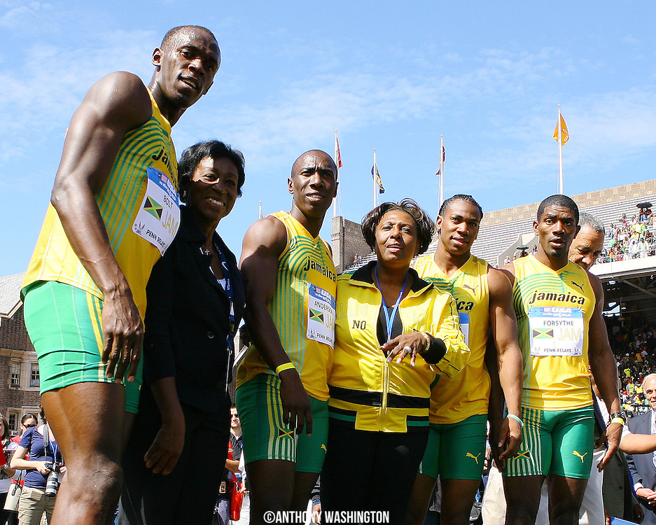 Jamaica's 4x100 relay team, from left, Usain Bolt, Marvin Anderson, Yohan Blake and Mario Forsythe pose for pictures with two unidentified women on the podium after winning the 4x100 relay at the Penn Relays athletics meet on Saturday, April 24, 2010, in Philadelphia, PA.