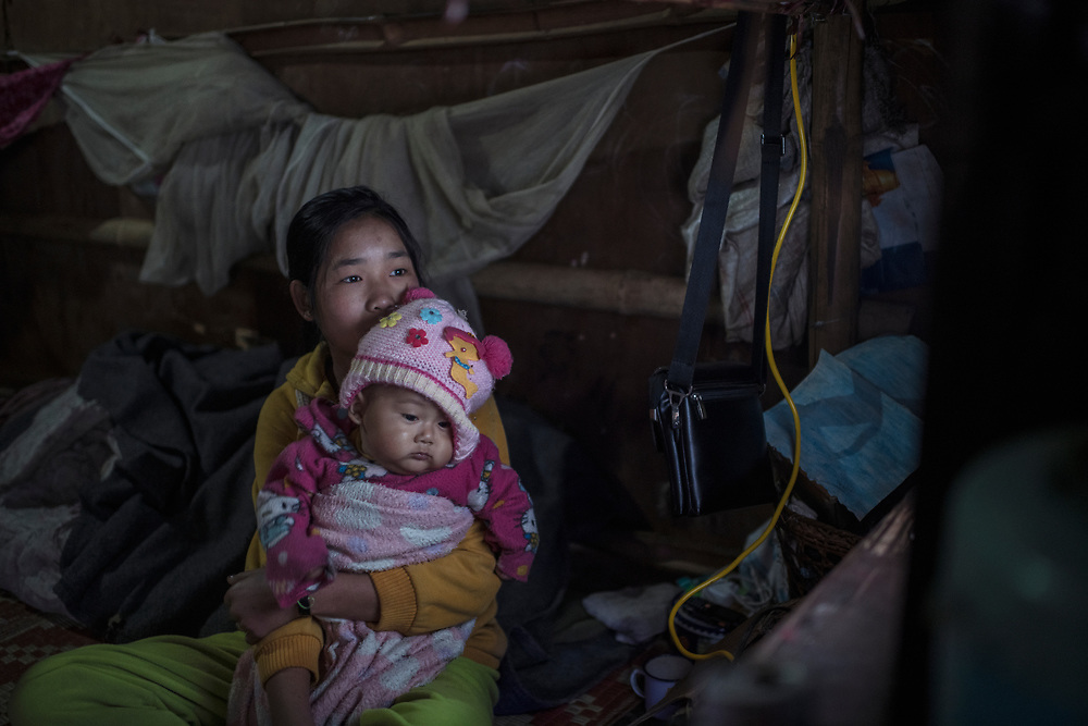 Laiza, Myanmar 20180130 <br /> Bawk Ja, 15, and her baby cousin watching tv before school, in the Je Yang IDP Camp outside Laiza. The conflict have driven hundreds of thousands of people on the run, with several camps for Internally Displaced People (IDP) scattered along the border with China.<br /> Photo: Vilhelm Stokstad / Kontinent