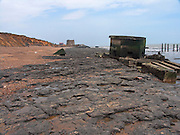 Rapid coastal erosion at East Lane, Bawdsey, Suffolk, England. Soft crag cliffs are easily eroded, dark underlying London clay is exposed. The second world war pill box indicates where the coast was around ten years ago..