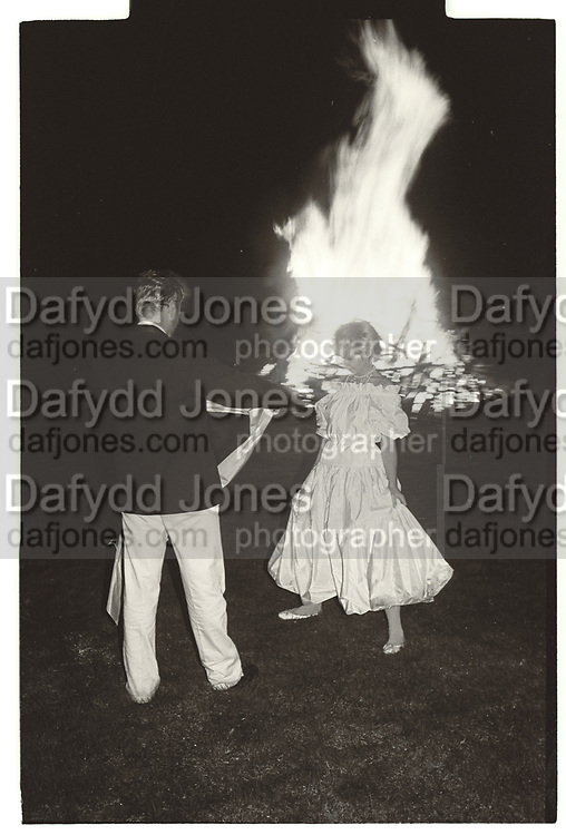 Couple in front of bonfire. Terence Conran's 50th birthday. Kintbury. 1981.