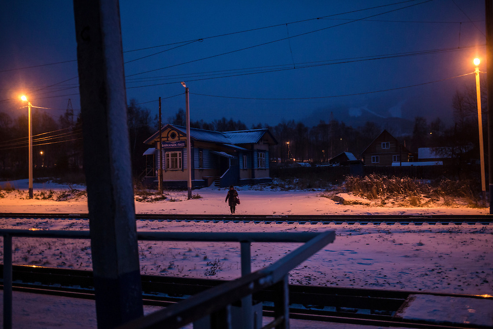 A woman crosses the train tracks following a snowstorm on Sunday, October 20, 2013 in Baikalsk, Russia.