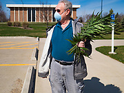 "05 APRIL 2020 - DES MOINES, IOWA:  A parishioner of Luther Memorial Church walks home after picking up palms at a drive through Palm Sunday service sponsored by Luther Memorial Church on the campus of Grand View University in Des Moines. About 150 people attended the service. They remained in their cars while the ministers read a short passage from the Bible, handed out palms and blessed them. On Sunday, 05 April, Iowa reported 868 confirmed cases of the Novel Coronavirus (SARS-CoV-2) and COVID-19. There have been 22 deaths attributed to COVID-19 in Iowa. Restaurants, bars, movie theaters, places that draw crowds are closed until 30 April. The Governor has not ordered ""shelter in place"" but several Mayors, including the Mayor of Des Moines, have asked residents to stay in their homes for all but essential needs. People are being encouraged to practice ""social distancing"" and many businesses are requiring or encouraging employees to telecommute.       PHOTO BY JACK KURTZ"