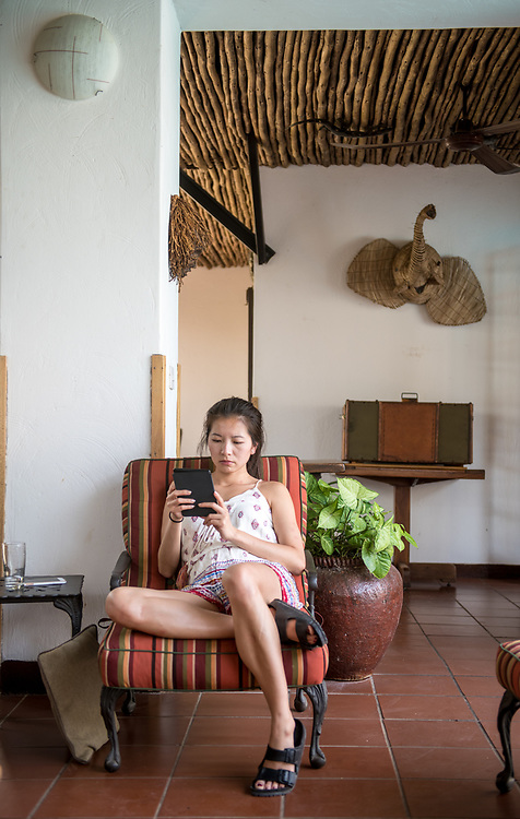An Asian-American woman sits in lounge chair inside a safari lodge in Kasane while using tablet, Botswana Chobe National Park - Botswana
