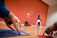 """8 Novembre, 2008. Brooklyn, New York.<br /> <br /> Due mamme con i relativi figli seguono un corso di yoga per famiglie con l'istruttrice Ute Kirchgaessner (sinistra) al Bend & Bloom Yoga a Park Slope, Brooklyn, NY. Park Slope, spesso definito dai newyorkesi come """"The Slope"""", è un quartiere nella zona ovest di Brooklyn, New York, e confinante con Prospect Park.  Park Slope è un quartiere benestante che ha il maggior numero di nascite, la qualità della vita più alta e principalmente abitato da una classe media di razza bianca. Per questi motivi molte giovani coppie e famiglie decidono di trasferirsi dalle altre municipalità di New York a Park Slope. Dal punto di vista architettonico, il quartiere è caratterizzato dai brownstones, un tipo di costruzione molto frequente a New York, e da Prospect Park.<br /> <br /> ©2008 Gianni Cipriano for The New York Times<br /> cell. +1 646 465 2168 (USA)<br /> cell. +1 328 567 7923 (Italy)<br /> gianni@giannicipriano.com<br /> www.giannicipriano.com"""