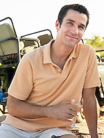 Portrait of mid-adult man holding wineglass smiling jeep in background