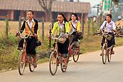 Mar. 13, 2009 -- VANG VIENG, LAOS: Girls pedal their bikes to school in Vang Vieng, Laos. Photo by Jack Kurtz