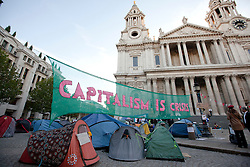 © Licensed to London News Pictures. 17/10/2011. LONDON, UK. An anti-capitalist banner and tents are seen outside St Paul's Cathedral as the Occupy London demonstration enters its third day. As part of a demonstration taking place in cities across the world Protesters occupied the square outside St Paul's Cathedral on Saturday (15/10/11) as part of a protests taking place in cities across the world demonstrating against the banks handling of the current ongoing financial crisis . Photo credit: Matt Cetti-Roberts/LNP