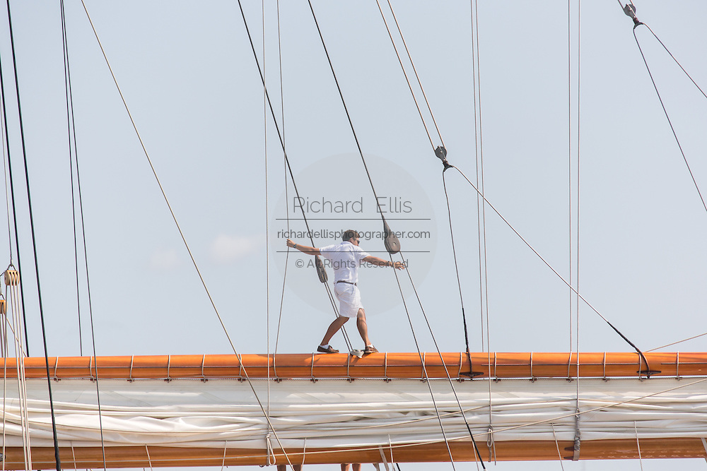 A deck hand walks on the main gaff spar on the 196-foot sailing yacht Germania Nova as it sails Charleston Harbor June 26, 2013 in Charleston, South Carolina.