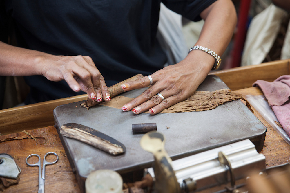 A worker at Cohiba factory 'El Laguito' in Havana, rolls up a Cohiba cigar with her hands during her work shift.