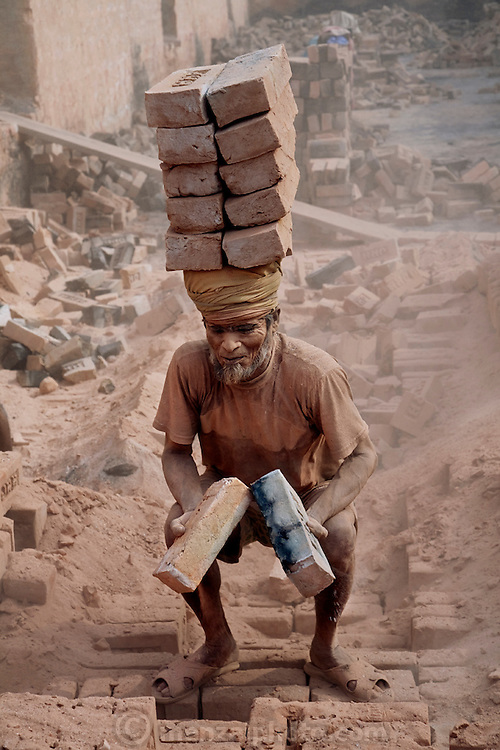 A brick hauler loads a stack of bricks at the JRB brick factory near Sonargaon, outside Dhaka, Bangladesh. (From the book What I Eat: Around the World in 80 Diets.) The heavy clay soils along the river near the market town of Sonargaon are well suited for making bricks. At the JRB brick factory, workers of all ages move raw bricks from long, stacked rows, where they first dry in the sun, to the smoky coal-fired kilns. After being fired, the bricks turn red. A foreman keeps tally, handing the workers colored plastic tokens corresponding to the number of bricks they carry past him. They cash in the chips at the end of each shift, taking home the equivalent of $2 to $4 (USD) a day.
