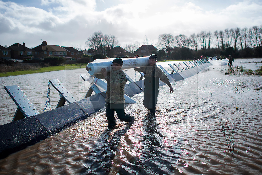 &copy; London News Pictures. Staines, UK. 15/02/2014.<br /> Soldiers from  2nd Royal Tank Regiment and The Gurkhas   installing Geodesign flood barriers in Staines, which have been brought in from Sweden to help control flood waters. The barriers were designed by Sten-Magnus Kullberg (pictured in set).  Photo credit: Ben Cawthra/LNP