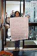 Roma, 13 Nov 2014<br /> Terzo giorno di tensioni tra italiani ed immigrati ospiti nel centro di accoglienza per rifugiati nel quartiere di Tor Sapienza. Una donna, residente nel quartiere, davanti all'ingresso  del  centro di accoglienza per rifugiati. Sul cartello la scritta: Scudo umano contro il razzismo.<br /> Rome, Italy. 13th November 2014<br /> Third day of tensions between Italian  and immigrants guests in the migrant reception center in the neighborhood of Tor Sapienza. A woman, who lives in the neighborhood, at the entrance  the migrant reception center. The sign read: human shield against racism