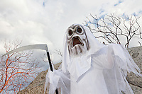 Boy dressed up as grim reaper holding scythe