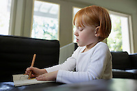 Young girl (5-6) drawing at desk