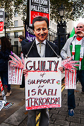 Downing Street, London, November 15th 2014. Dozens of Palestinians and their supporters faced a small group of Israeli counter protesters as they demonstrated outside the gates of Downing Street against Israel. Police had to intervene as several from both sides took exception to what was being said, with the half-dozen-strong Israeli group eventually moving off. Pictured: A protester wears a David Cameron mask accusing the PM of having blood on his hands