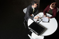 Businessman conferring with woman at round table elevated view