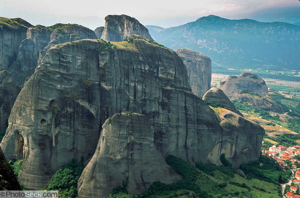"""The weird rock spires of Meteora rise above the village of Kastraki, near Kalambaka, in central Greece, Europe. Meteora (which means """"suspended in the air"""") is a complex of six Eastern Orthodox Christian monasteries built by medieval monks on natural rock pillars near Kalambaka, in central Greece, Europe. The sandstone and conglomerate of Meteora were formed in the cone of a river delta estuary emerging into a sea about 60 million years ago, then later uplifted and eroded into pinnacles. The isolated monasteries of Meteora helped keep alive Greek Orthodox religious traditions and Hellenic culture during the turbulent Middle Ages and Ottoman Turk occupation of Greece (1453-1829). UNESCO honored Meteora as a World Heritage Site in 1988. Visit early in the morning and in the off season to avoid crowds."""