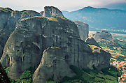 "The weird rock spires of Meteora rise above the village of Kastraki, near Kalambaka, in central Greece, Europe. Meteora (which means ""suspended in the air"") is a complex of six Eastern Orthodox Christian monasteries built by medieval monks on natural rock pillars near Kalambaka, in central Greece, Europe. The sandstone and conglomerate of Meteora were formed in the cone of a river delta estuary emerging into a sea about 60 million years ago, then later uplifted and eroded into pinnacles. The isolated monasteries of Meteora helped keep alive Greek Orthodox religious traditions and Hellenic culture during the turbulent Middle Ages and Ottoman Turk occupation of Greece (1453-1829). UNESCO honored Meteora as a World Heritage Site in 1988. Visit early in the morning and in the off season to avoid crowds."
