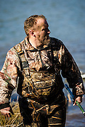 Gary Friend from Bartlesville, OK wades to shore after retrieving decoys while duck hunting in Shamrock, Oklahoma