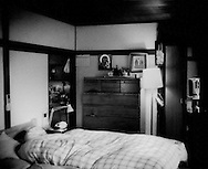 "The Tokyo apartment of Russian Orthodox priest, Iliya Toru Takei on the grounds of the Holy Resurrection Cathedral in Ochanomizu mixes Japanese sliding ""fusuma"" doors with a western style bed in Russian Orthodox icons.  Tokyo, Japan.."