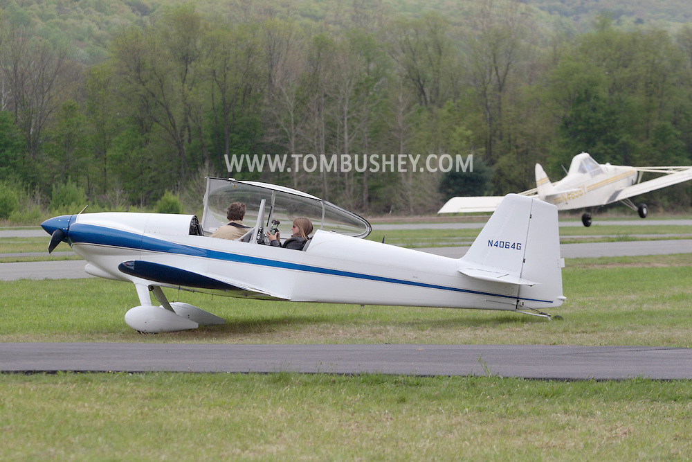 Wurtsboro, NY - A pilot and passenger in a 2001 Mullaney Robert S RV-4 get ready to fly as another plane takes off in the background at the grand reopening of Wurtsboro Airport on May 11, 2008.