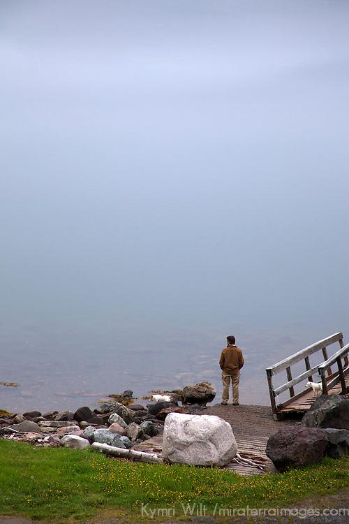 North America, Canada, Nova Scotia, Guysborough. A man stands at foggy water's edge in Guysborough.