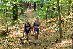Two girls walk on a woodland trail near Page Pond in Meredith, New Hampshire.