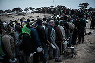 After crossing  border from Libya, migrants workers arrive in an UNHCR transit camp in Choucha, walking 7 km from Tunisia's Ras Jdir border station. They will be kept in this camp waiting for repatriation to their home countries. Migrants line up for meal distribution.<br /> 03 March 2011.