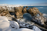 Coast with basaltic rock arches und surf in the winter, village Arnarstapi, peninsula Snaefellsnes, Iceland