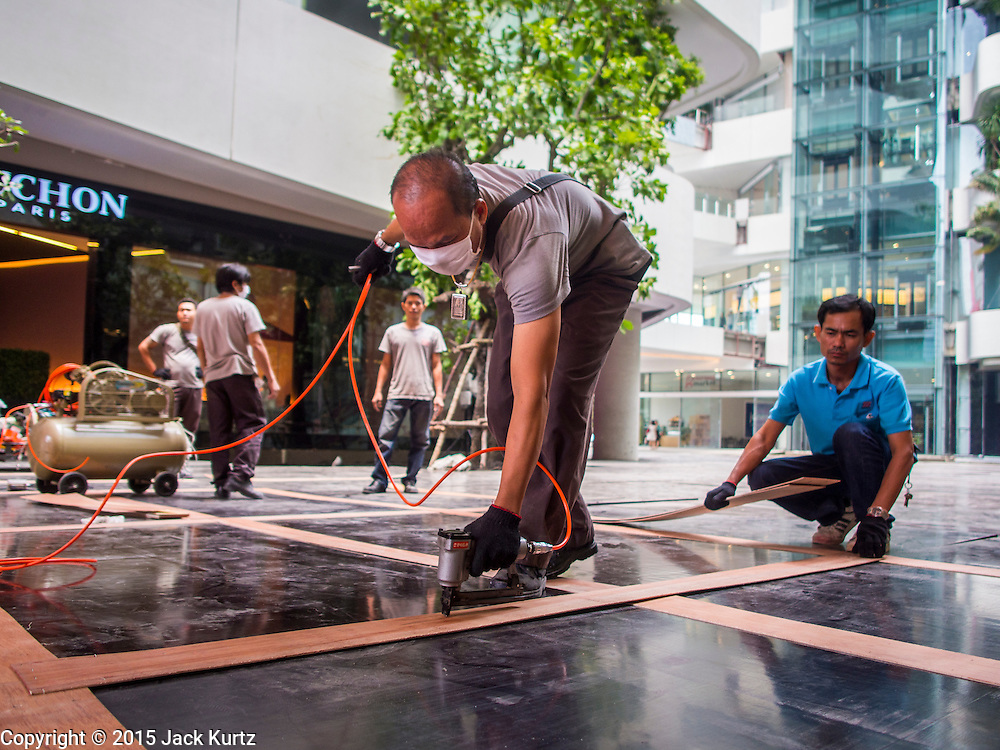 "27 MARCH 2015 - BANGKOK, THAILAND:  Construction workers install flooring on during the grand opening of ""EmQuartier"" a new mall in Bangkok. ""EmQuartier"" is across Sukhumvit Rd from Emporium. Both malls have the same corporate owner, The Mall Group, which reportedly spent 20Billion Thai Baht (about $600 million US) on the new mall and renovating the existing Emporium. EmQuartier and Emporium have about 450,000 square meters of retail, several hotels, numerous restaurants, movie theaters and the largest man made waterfall in Southeast Asia. EmQuartier celebrated its grand opening Friday, March 27.    PHOTO BY JACK KURTZ"
